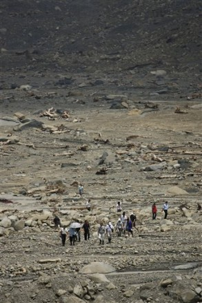 Villagers walk through the landslide as exiled Tibetan spiritual leader the Dalai Lama, unseen, prays for victims killed in Typhoon Morakot, at the destroyed village of Shiao Lin, in southern Taiwan, Monday, Aug. 31, 2009. (AP Photo/Wally Santana)