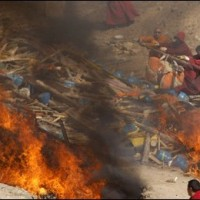 Tibetan monks throw a body wrapped in cloth during a mass cremation for victims of Wednesday's earthquake in the Yushu Tibetan Autonomous Prefecture (Tibetan:Kyigudo), Saturday, 17 April 2010. (AP Photo/Andy Wong)