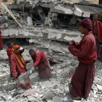 Tibetan monks help digging to search students believe to be trapped at a school collapsed after an earthquake in Kyigudo on Friday, 16 April 2010/AP