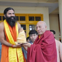 Swami Ramdev receives a souvenir from Kalon Tripa during a function at the main temple