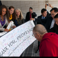 His Holiness the Dalai Lama is presented with a card signed by students during a break in the