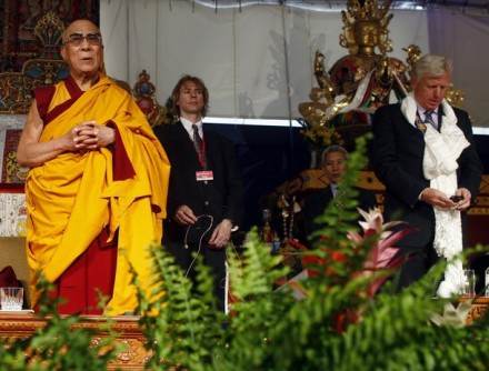 Toronto Mayor David Miller (R) checks his cell phone while singing the Canadian national anthem beside His Holiness the Dalai Lama during a ceremony at the Tibetan Canadian Cultural Centre in Toronto on