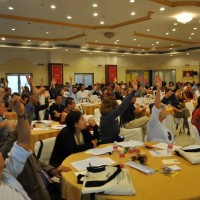Participants raise their hands to support resolutions passed during the Sixth International Conference