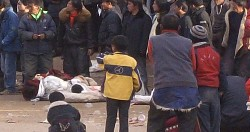 Onlookers watch dead bodies of Tibetans shot down by Chinese security forces on March 16, 2008 in Ngaba, phayul file photo