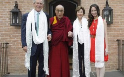 The Dalai Lama grasped his hosts' hands for a photo Tuesday. Former President George W. Bush, his wife, Laura, and daughter Barbara welcomed the Tibetan spitual leader to their Preston Hollow home. Photo/Layne Murdoch