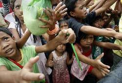 Residents line up for relief supplies at an evacuation center in Iligan City, Philippines on December 19, 2011. (AP/Bullit Marquez