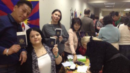 Tibet supporters from Russia displaying their blue book to express solidarity with Tibet.